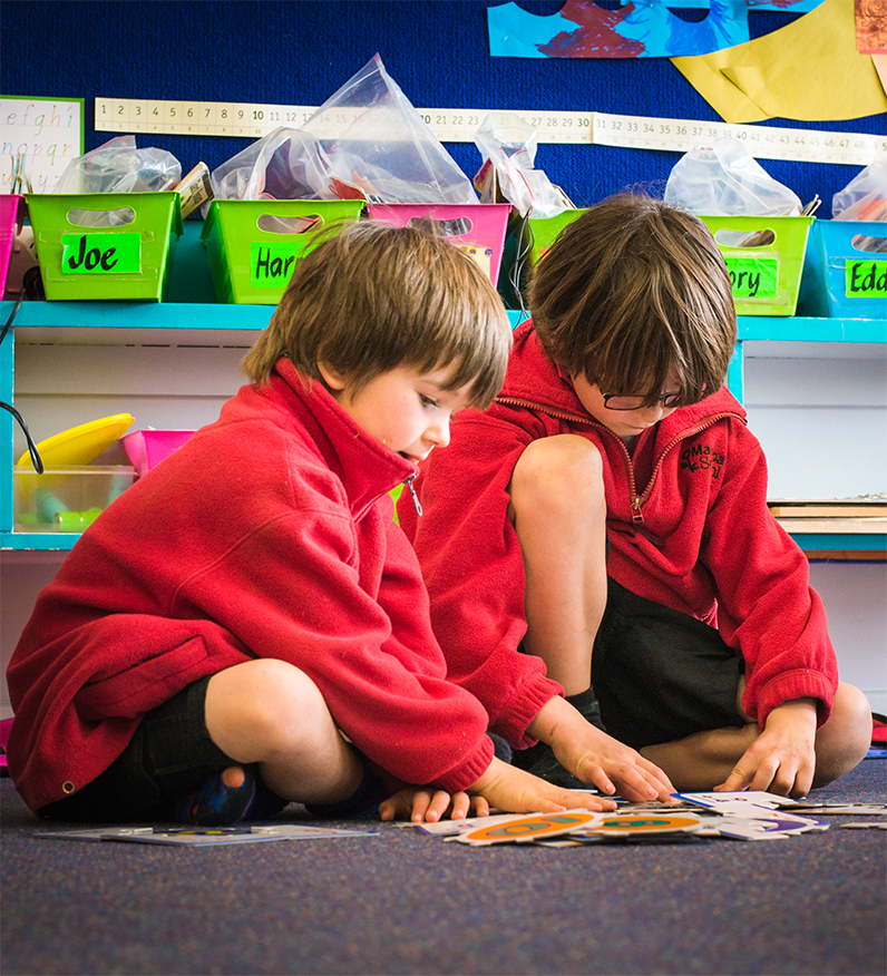 Two Mararoa school boys sitting on the floor doing a puzzle together